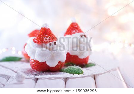 Christmas Strawberry Santa Dessert stuffed with whipped cream. Funny Winter New year Gourmet food. Cheesecake. Xmas party food idea, dinner table setting. Happy Winter Holiday served table.