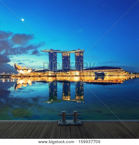 Singapore, Republic of Singapore - May 4, 2016: Marina Bay Sands hotel glowing at night with wooden pier on foreground