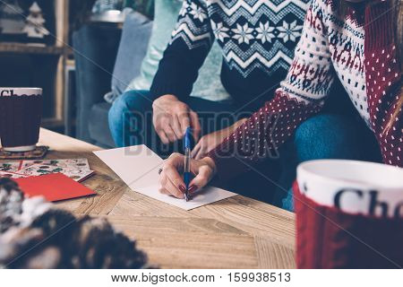 Young couple in sweaters enjoying Christmas atmosphere while writing greetings.