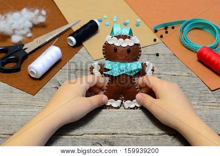 Child holding a cute gingerbread man ornament in his hands. Christmas tree gingerbread man ornament, handicrafts supplies on old wooden table. Christmas felt diy for kids. Homemade sewing concept