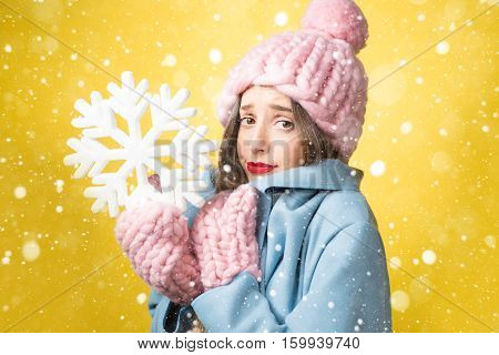 Confused and unhappy woman in colorful winter clothes holding a snowflake on the yellow background