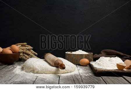 Dough with wooden rolling pin flour and eggs on a wooden table on a dark background with copy space