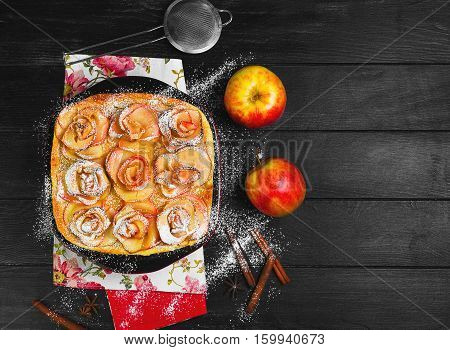Fruit apple pie tartlet (cake). On top of the pie cake in the shape of apples rose flowers. Fresh fruit apples for pie cake. The dark black wooden background. Top view. Flat lay.
