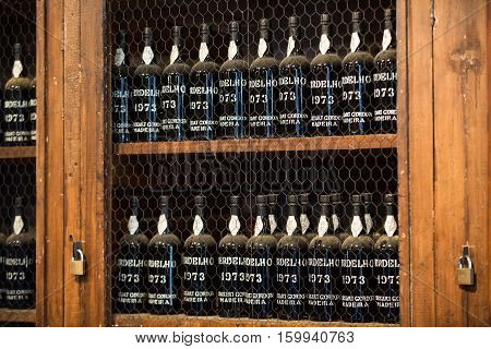 FUNCHAL MADEIRA PORTUGAL - SEPTEMBER 1 2016: Museum - repository of expensive vintage wine Madera. Long rows of shelves made of bottles of wine. funchal Madera. Portugal