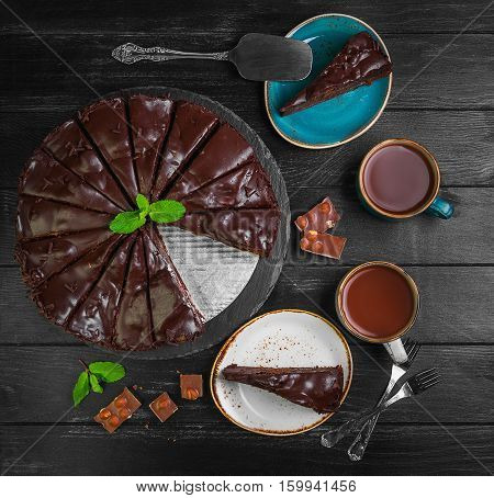 Big chocolate cake torte. Ingredients for chocolate cake torte mint chocolate chips. Slices chocolate cake on saucer. Drink hot chocolate cocoa (coffee) in cups. Black wooden background. Top view.