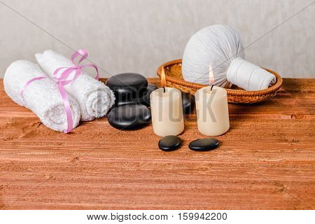 Spa Composition Of White Towels, Candles, Thai Herbal Compress Ball In Basket And Zen Basalt Stones