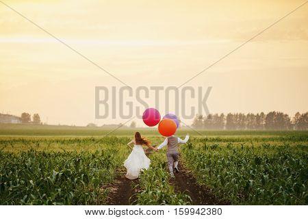 Wedding Couple Running Away On The Field