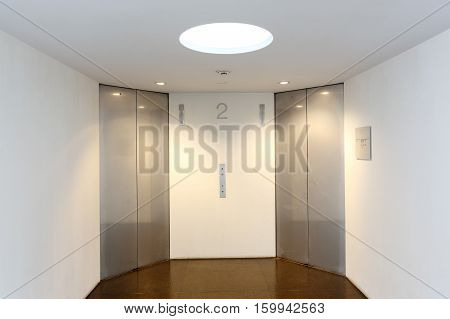 Two modern elevator with closed metal doors