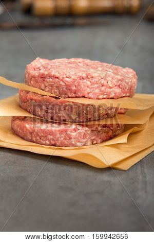 Close up raw ground beef meat cutlets on a stone surface