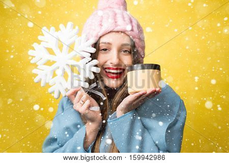 Colorful winter portrait of a beautiful woman with facial cream and snowflake on the yellow background. Face skin care in winter