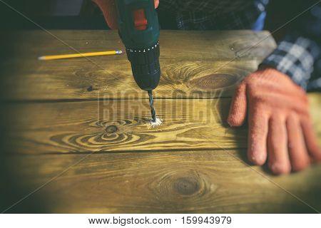 Man drills the wooden plank