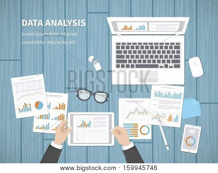 Man analyzes documents. Accounting, analytics, market analysis, report, research, planning concept. Hands on the desktop hold tablet. Charts, diagrams, graphs on the paper. Office space top view.