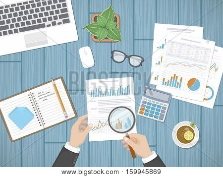 Auditing concepts. Businessman auditor inspects assessing financial documents. Man's hands with magnifying glass above graphics and charts. Research,management, analysis, data, planning, accounting