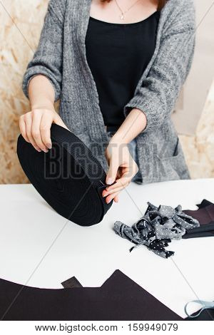 Unrecognizable tailor holding elastic band close-up. Fashion designer preparing for sewing clothes. Garment industry, tailoring process, clothes making atelier concept