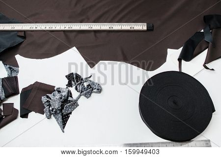 Pattern cutting designer workplace flat lay. Top view on tailor table with dark fabric, measuring tape and ribbon roll. Clothes making, fashion atelier, garment industry concept