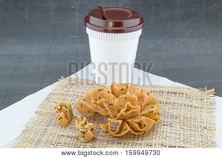 Crispy Lotus Blossom Cookie with Take a way cup of coffee Rush hour in the morning food and drink