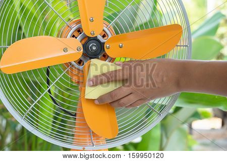 Woman Cleaning electric fan Housework at home