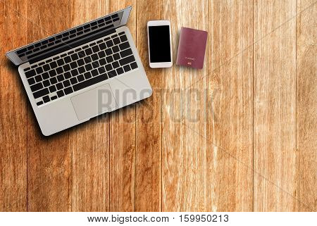 Laptop computersmart phone and passport on wood table top view with copy space.Office supplies and gadgets on desk table.Working desk table concept.