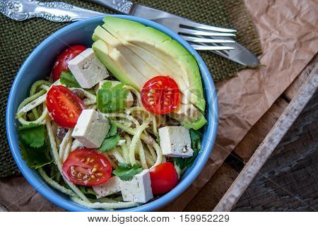 Vegan zucchini pasta in a bowl with tofu tomatoes avocado and herbs. Perfect for the detox diet or just a healthy meal. Love for a healthy raw food concept.