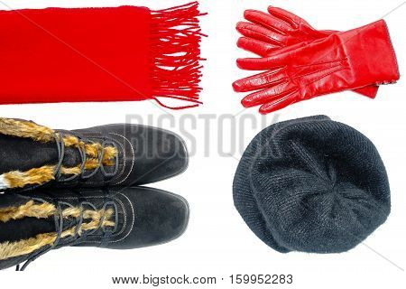 Flat Lay of women black winter boots a red cashmere scarf a black angora cap and red leather gloves isolated on white background.