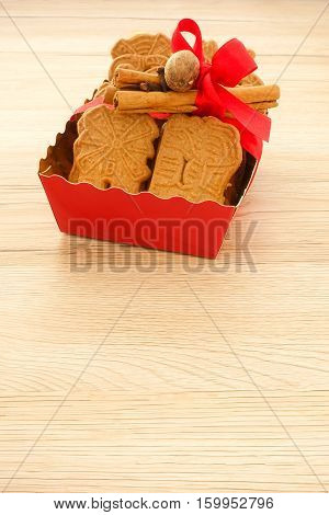 Red tray full of spiced biscuits with almonds Spekulatius mit Mandeln decorated with a red Christmas bow cinnamon sticks cloves and muscat. Backlit light brown wooden background and lots of copy space.