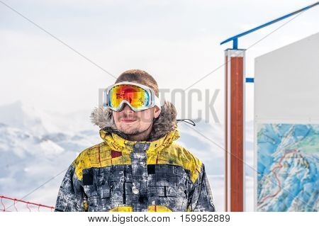 Young man in ski goggles outdoors with French Alps covered with snow at background. Val-d'Isere, France