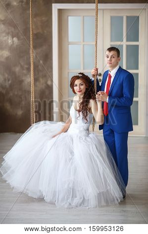 Wedding. Happy young bride sitting on swing and groom. Marriage concept