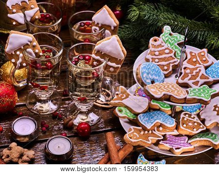 Lot of Christmas cookies in Tiered Cookie Stand in the foreground. Tea and wine in the background.