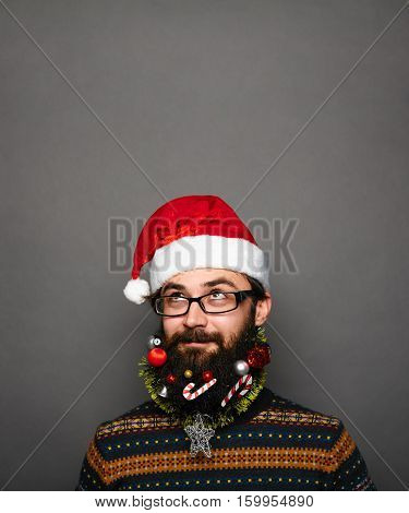 Funny Bearded man in santa hat looking up to blank space over grey background.