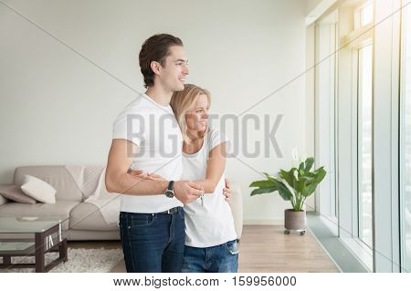 Young happy couple, holding a key, purchased a new apartment, rather than throw money away on rent, flat as the biggest investment, planning a future, preparing a housewarming party poster