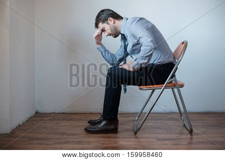 Desperate And Pensive Businessman Seated On A Chair
