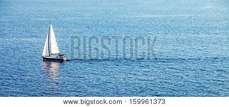 Alone white boat in the blue ocean
