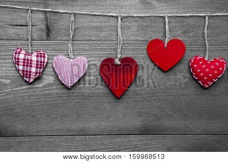 Wooden Background With Red Hearts Hanging In A Row. Black And White Style With Colored Hot Spots. Copy Space For Advertisement Or Free Text. Greeting Card For Valentines Or Mothers Day