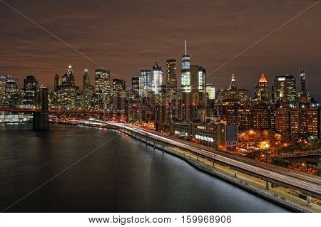 View of Lower Manhattan with Brooklyn Bridge and FDR Drive at night.