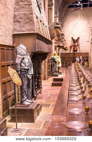 Leavesden, London, UK - 1 March 2016: Interior of the Great Hall (Dining Hall) of Hogwarts. Fire place and table. Warner Brothers Studio display of decorations for Harry Potter film