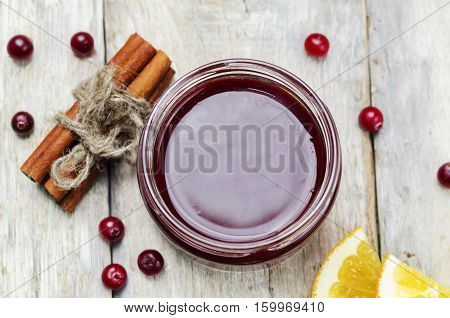 Orange cinnamon honey cranberry sauce on wood background.