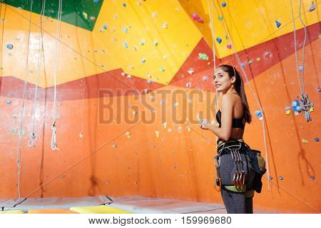 Get over it. Overjoyed young delighted woman preparing to climb up the wall while wearing climbing equipment and smiling.