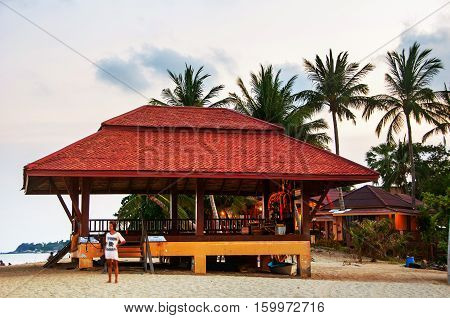 Summer resort at Ko Samui, Thailand. Little bungalow hidden in the trees with water at sunset at the beach