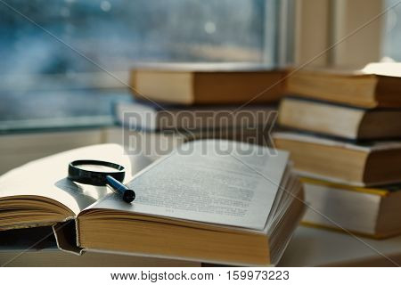 open hardcover book magnifying glass on the window