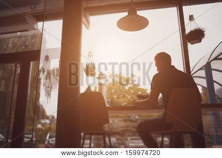 Silhouette of a man working at laptop while sitting in cafe. Yellow Light flare effect