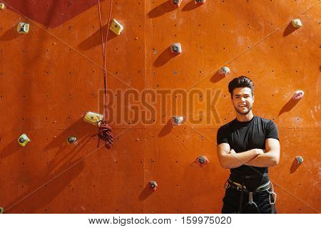 Style and sport. Young active joyful man posing near climbing wall while standing in climbing gym and smiling.