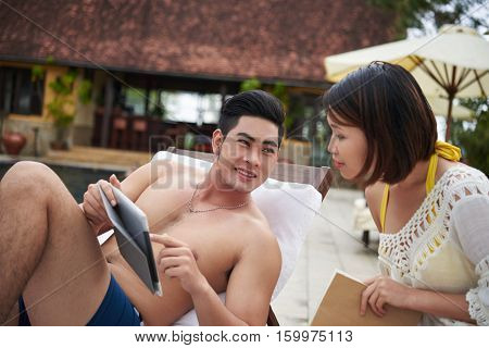 Handsome Asian man showing something interesting on tablet to his girlfriend