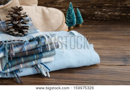 View of blue cashmere sweater wool square scarf ugg boots little christmas tree and natural fir cone on wooden background. Concept of Winter time and Christmas holiday. Copy space.