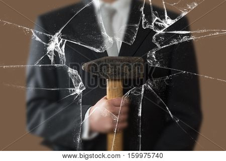 Business Man With Sladgehammer Behind A Broken Window