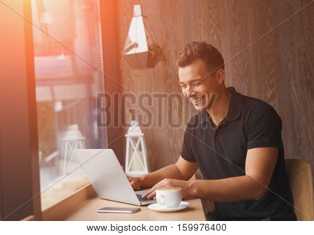 Successful entrepreneur smiling in satisfaction as he checks information on his laptop computer while working inside a cafe with sun flare