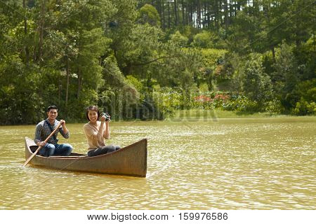 Happy young couple enjoying boating on the rive