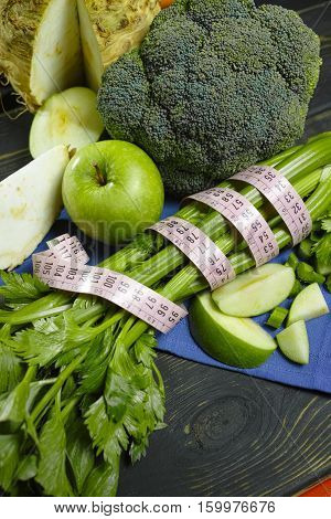 Green vegetables and fruits - celeriac broccoli celery shoots and apples healthy fitness diet concept