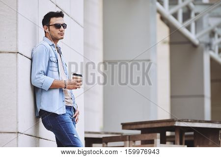 Young man with take-out coffee standing outdoors