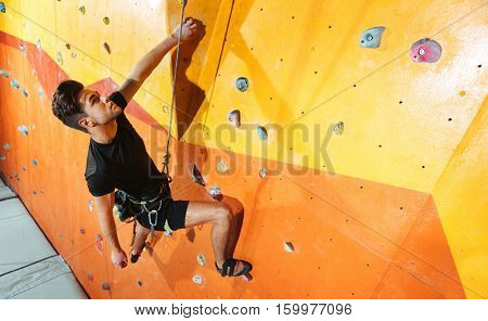 Dexterity and strength. Serious handsome young man spending time in climbing gym while climbing up the wall and using equipment.