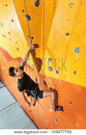 Harmony and strength. Equipped handsome young man spending time in climbing gym while climbing up the wall and using insurance ropes.